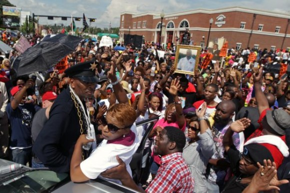Michael Brown's mother, Lesley McSpadden (bottom, in white shirt) acknowledges the crowd of protesters gathered in front of the police department on Saturday, Aug. 30, 2014, in Ferguson. Photo by Huy Mach, hmach@post-dispatch.com