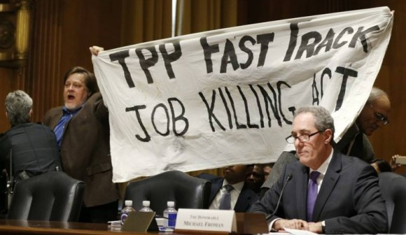 TPP Protest Froman miffed as KZ and Dick Ochs hold banner behind him. Source Reuters.